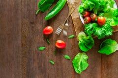 Salatgemüse in der Schüssel mit Gabeln auf Weinleseschmutzholztisch stockfotos