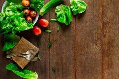 Salatgemüse in der Schüssel mit Gabeln auf Weinleseschmutzholztisch stockbild