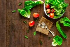 Salatgemüse in der Schüssel mit Gabeln auf Weinleseschmutzholztisch lizenzfreies stockfoto