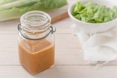 Salatsoße in einem Glasbehälter auf hellem hölzernem Hintergrund Lizenzfreies Stockfoto