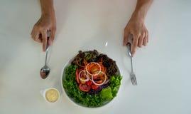 Salatteller mit buntem Gemüse mit Sahne Soße und Geräte diente auf einer weißen Tabelle vor Männern stockfotografie