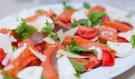 Salattomaten, Käse, Meeresfrüchte im weißen Teller auf der Feiertagstabelle Stockfotografie