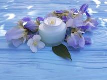 Salben-Irisblume der Sahnefeuchtigkeitscreme kosmetische auf einem blauen hölzernen Hintergrund Lizenzfreie Stockbilder