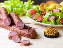 Salchicha ahumada con la ensalada de las verduras en un tablero de madera Fotografía de archivo libre de regalías