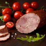 Salchicha ahumada con las verduras: tomates de cereza y lechuga del ` s del cordero Fotografía de archivo