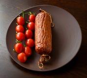 Salchicha ahumada con los tomates de cereza en una placa Fotografía de archivo libre de regalías