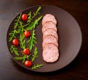 Salchicha ahumada con los tomates de cereza y la lechuga del ` s del cordero Imagen de archivo