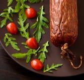 Salchicha ahumada con los tomates de cereza y la lechuga del ` s del cordero Imagenes de archivo