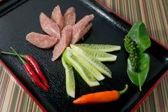 Salchicha amarga tailandesa tailandesa con los chiles y el pepino Imagenes de archivo