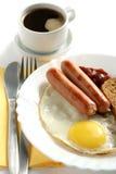 Salchicha con el huevo y una taza de café Imágenes de archivo libres de regalías