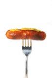 Salchicha con la mostaza en fork Foto de archivo