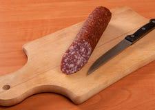 Salchicha cortada con el cuchillo en una tabla de madera Imagen de archivo libre de regalías