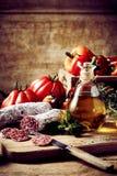 Salchicha cortada con el tarro de aceite y de tomates Foto de archivo libre de regalías