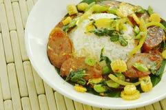 Salchicha de cerdo china sofrita picante con la hoja y el arroz de la albahaca en la placa foto de archivo