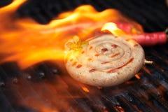 Salchicha del Cumberland, salchicha de cerdo espiral en parrilla del Bbq con la llama, Imagen de archivo
