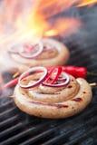 Salchicha del Cumberland, salchicha de cerdo espiral en parrilla del Bbq con la llama, Imagen de archivo libre de regalías