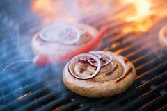 Salchicha del Cumberland, salchicha de cerdo espiral en parrilla del Bbq con la llama, Fotos de archivo libres de regalías