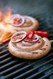 Salchicha del Cumberland, salchicha de cerdo espiral en parrilla del Bbq con la llama, Foto de archivo libre de regalías