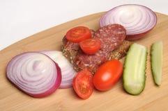 Salchicha del verano, pan, pepino salado, tomates de cereza rojos y cebolla roja cortada en la tabla de cortar de bambú Fotografía de archivo libre de regalías