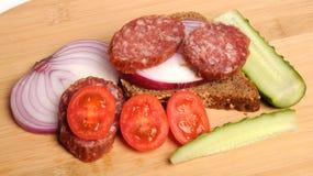 Salchicha del verano, pan, pepino salado, tomates de cereza rojos y cebolla roja cortada en la tabla de cortar de bambú Fotografía de archivo