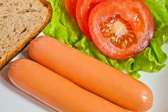 Salchicha en lechuga verde con pan y el tomate Foto de archivo