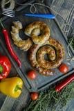 Salchicha frita con las hierbas y las especias, fondo de madera Anillo de la salchicha hecha en casa cocida Servido en un tablero foto de archivo libre de regalías