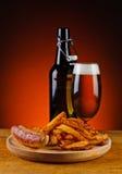 Salchicha, patatas fritas y cerveza asadas a la parrilla Fotos de archivo