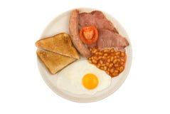 Salchicha, tocino, huevo, tomate, habas y tostada imagenes de archivo
