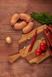 Salchicha, tomates y especias en una tabla de madera Fotografía de archivo