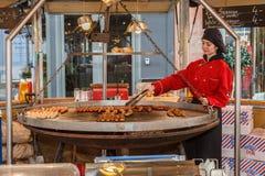 Salchichas alemanas que cocinan en una parrilla de balanceo gigante Fotografía de archivo libre de regalías