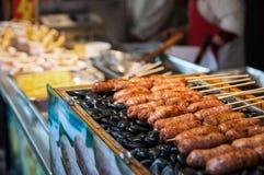 Salchichas asadas a la parilla El primer de la salchicha se preparó en piedras en el mercado de China Alimento chino de la calle Fotos de archivo