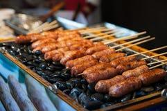 Salchichas asadas a la parilla El primer de la salchicha se preparó en piedras en el mercado de China Alimento chino de la calle Fotografía de archivo libre de regalías