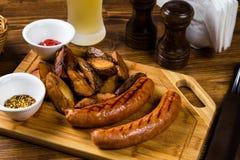 Salchichas asadas a la parrilla con la patata de la carne asada con las especias Fotografía de archivo libre de regalías