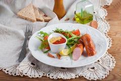 Salchichas asadas a la parrilla con la salsa de tomate, la mostaza y la ensalada Imagen de archivo
