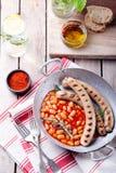Salchichas asadas a la parrilla con las habas en salsa de tomate Imagenes de archivo
