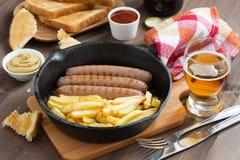 Salchichas asadas a la parrilla con las patatas fritas en un sartén, tostadas Fotografía de archivo libre de regalías