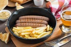 Salchichas asadas a la parrilla con las patatas fritas en un sartén, tostadas Fotos de archivo
