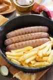 Salchichas asadas a la parrilla con las patatas fritas en un sartén, vertical Fotos de archivo libres de regalías