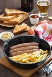 Salchichas asadas a la parrilla con las patatas fritas, tostada y cerveza, verticales Foto de archivo libre de regalías