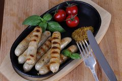 Salchichas asadas a la parrilla con los tomates, la mostaza y la albahaca en un fondo de madera Imagen de archivo libre de regalías
