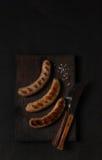 Salchichas asadas a la parrilla en una opinión superior oscura del tablero de madera Imagen de archivo