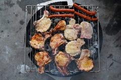 Salchichas, cerdo y carne del pollo en una parrilla Foto de archivo libre de regalías