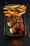 Salchichas con la salsa de curry y las patatas fritas adornadas en una placa Foto de archivo