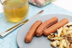 Salchichas con las patatas fritas Fotos de archivo libres de regalías