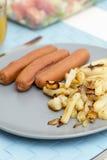 Salchichas con las patatas fritas Foto de archivo libre de regalías