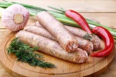 Salchichas crudas para asar a la parrilla en un tablero de madera con las verduras picantes Fotos de archivo