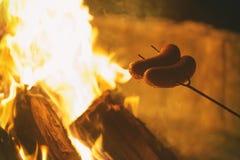 Salchichas de la asación en la hoguera Foto de archivo libre de regalías