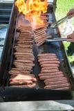 Salchichas de la parrilla de la llama en una barbacoa foto de archivo libre de regalías