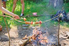 Salchichas en fondo de la hoguera del palillo Olor ahumado de la comida asada Cómo asar las salchichas con las verduras Roasty to fotos de archivo