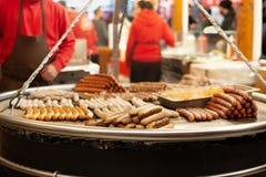 Salchichas en parrilla en la igualación del mercado de la Navidad foto de archivo
